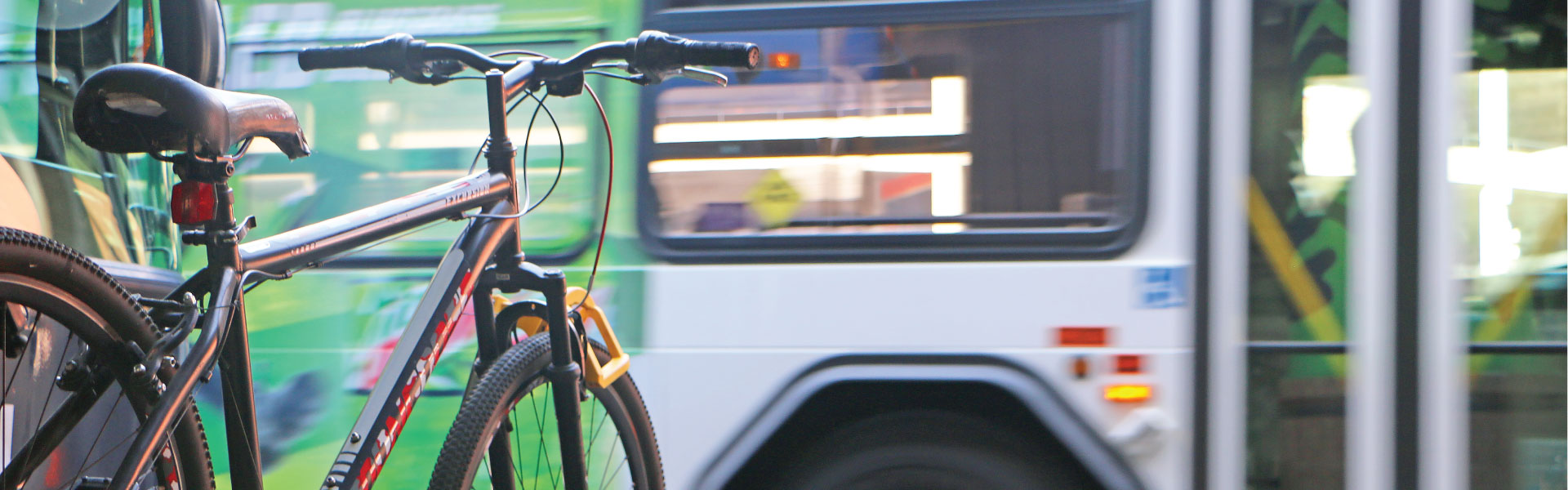 A bicycle attached to a bike rack on the front of a Lextran bus.