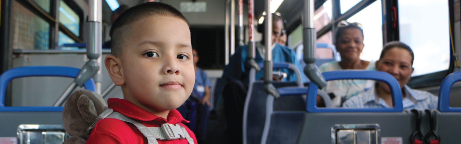 A small child standing on a bus and wearing a child harness.