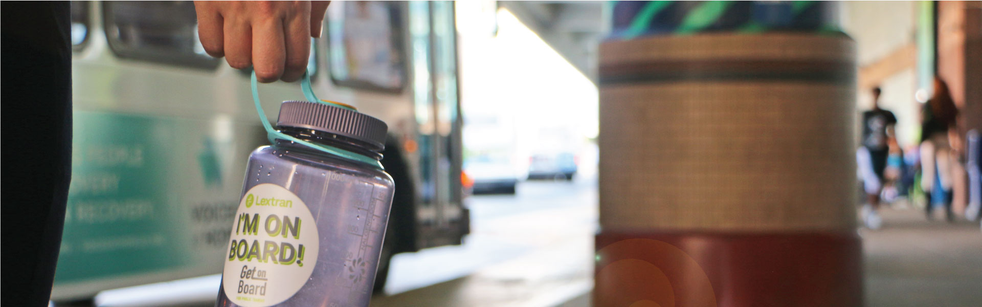 A person holding a water bottle with a Lextran sticker on it.