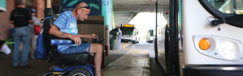 A man in a power chair driving on the ramp to enter the bus.
